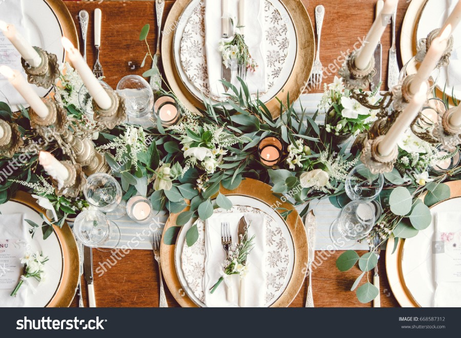 stock-photo-aerial-view-of-winter-green-garland-on-a-wedding-receptions-head-table-with-gold-place-setting-and-668587312.jpg